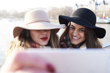 UK, London, two women wearing floppy hats taking a selfie on Millennium Bridge - IGGF01136