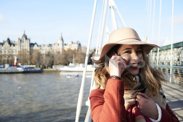 UK, London, stylish young woman talking on cell phone on Millennium Bridge - IGGF01139 - Ivan Gener/Westend61