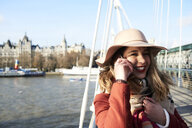 UK, London, stylish young woman talking on cell phone on Millennium Bridge - IGGF01139