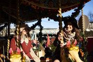 Two happy women having fun on a carousel - IGGF01142