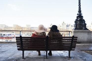 UK, London, rear view of two women sitting on a bench at River Thames promenade - IGGF01145