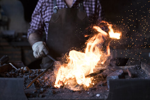Close-up of blacksmith working at forge in his workshop - ABZF02305