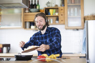 Young man with beard and plaid shirt, and headset cooking vegetables in kitchen - SGF02364