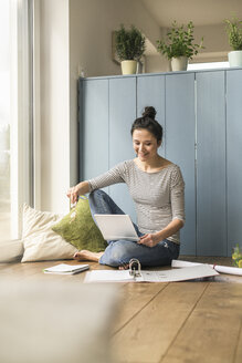 Smiling woman sitting at the window at home working with laptop and file folder - UUF17169