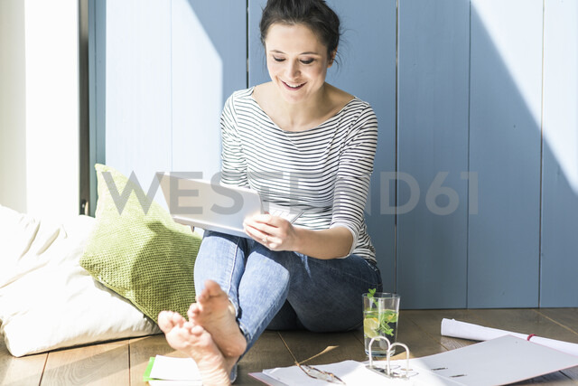 Smiling woman sitting at the window at home working with laptop and file folder - UUF17175 - Uwe Umstätter/Westend61