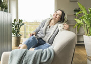 Happy woman with a mug and tablet sitting on the couch at home - UUF17220