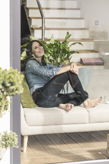Happy woman sitting on couch behind windowpane at home - UUF17229