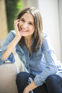 Portrait of happy woman wearing denim shirt at home - UUF17235