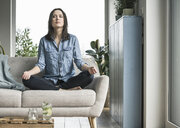 Woman sitting on the couch at home in yoga pose - UUF17238