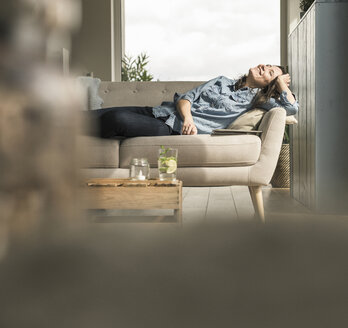 Happy woman lying on the couch at home - UUF17241