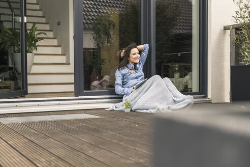 Happy woman wrapped in a blanket sitting on terrace at home with tablet - UUF17244