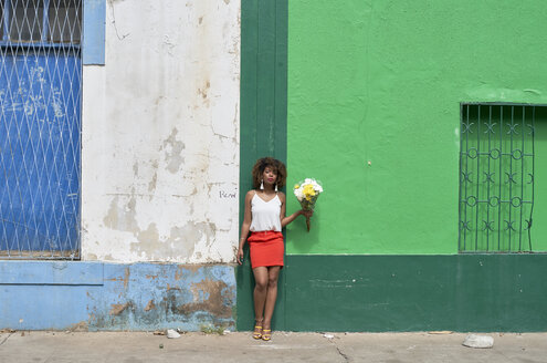 Afro woman on a green and blue wall holding flowers. Baixa, Moçambique, Maputo. - VEGF00004