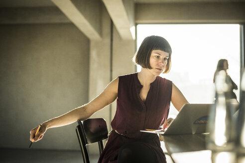 Pensive woman sitting in loft office, using laptop - MJRF00151