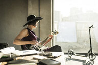 Woman with hat sitting in office, playing he guitar - MJRF00166