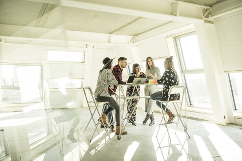 Group of creative professionals having a meeting in a bright office, discussing new solutions - MJRF00181
