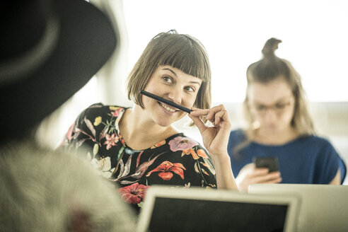 Colleagues having fun in office, making fun with a pencil moustache - MJRF00184