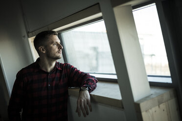 Young man looking out of window, daydreaming - MJRF00211