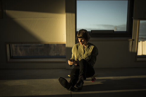 Businesswoman sitting on office floor at sunset, using smartphone - MJRF00226