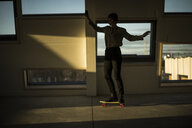 Businesswoman skateboarding at sunset in the office - MJRF00229