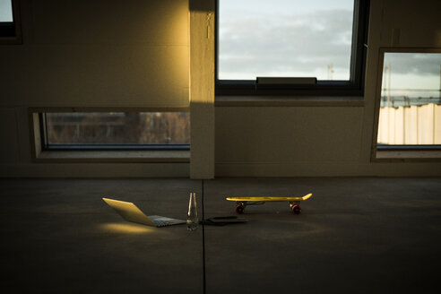 Laptop and skateboard in empty loft office at sunset - MJRF00232