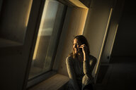 Woman sitting at office window at sunset, talking on the phone - MJRF00238