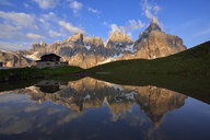 Italy, Trentino, Dolomites, Passo Rolle, Pale di San Martino range, Cimon della Pala with Baita Segantini reflecting in small lake in the evening - RUEF02123