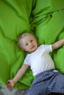 Portrait of little girl lying on green blanket in children's room - GAF00136