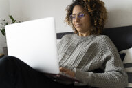 Woman sitting on bed, using laptop, surfing the net - FMOF00546