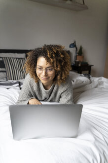 Woman lying on bed, using laptop, surfing the net - FMOF00549
