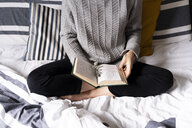 Woman sitting on bed, reading book - FMOF00552