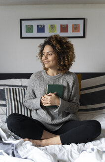 Woman sitting on bed, reading book - FMOF00558