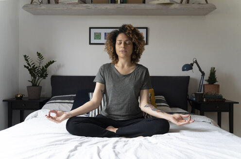 Woman practicing yoga, sitting on bed, meditating - FMOF00561