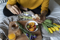 Woman sitting on bed, having a healthy breakfast - FMOF00567