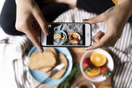 Woman sitting on bed, taking smartphone pictures of her haelthy breakfast - FMOF00573