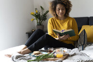 Woman sitting on bed, having a healthy breakfast, reading book - FMOF00579