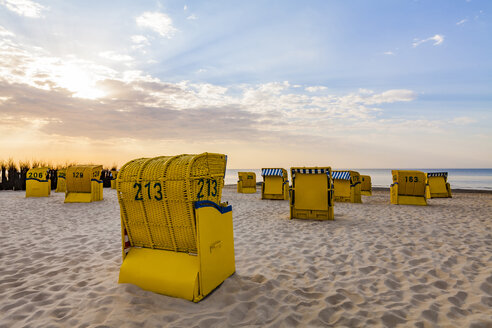 Germany, Lower Saxony, Cuxhaven, Duhnen, beach with hooded beach chairs at sunrise - WDF05241