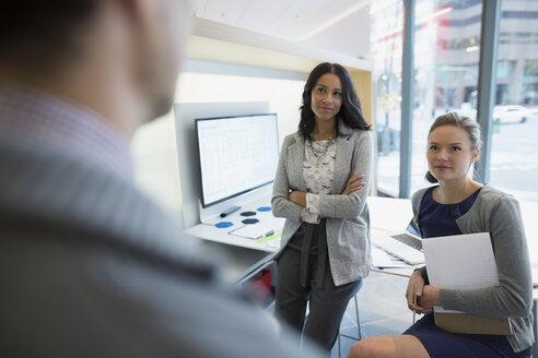 Businesswomen listening to coworker in office - HEROF35818
