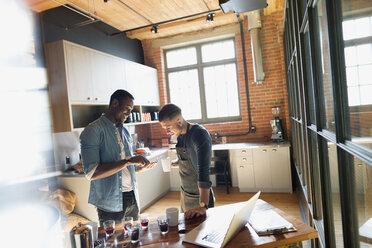 Entrepreneurial coffee roasters examining coffee beans in kitchen - HEROF35830