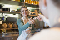 Customer paying bakery owner with credit card - HEROF35836
