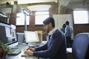 Creative businessman working at computer in office - HEROF35860