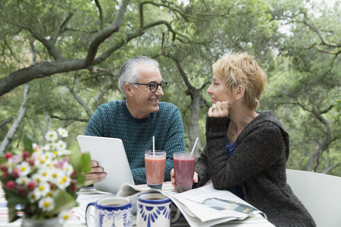 Couple drinking smoothies and reading newspaper and digital tablet on patio - HEROF35875