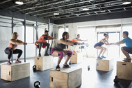Crossfit exercise class doing jump squats on boxes - HEROF35884