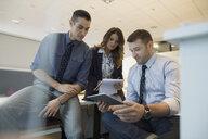 Business people using digital tablet in office cubicle - HEROF35893