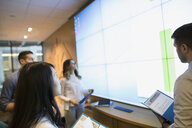 Business people looking up at projection screen - HEROF35902