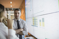 Business people discussing data on projection screen - HEROF35908