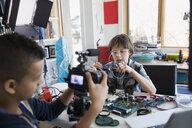 Boys videotaping circuit board assembly in bedroom - HEROF35935