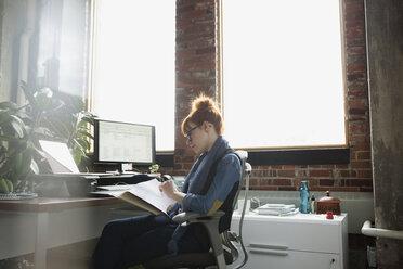Businesswoman reviewing paperwork at desk in office - HEROF35947