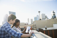 Businessman and businesswoman using digital tablet urban rooftop - HEROF35974