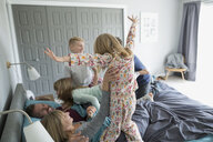 Playful children in pajamas jumping on parents in bed - HEROF36007