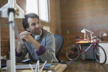 Pensive designer with headphones at desk in office - HEROF36028